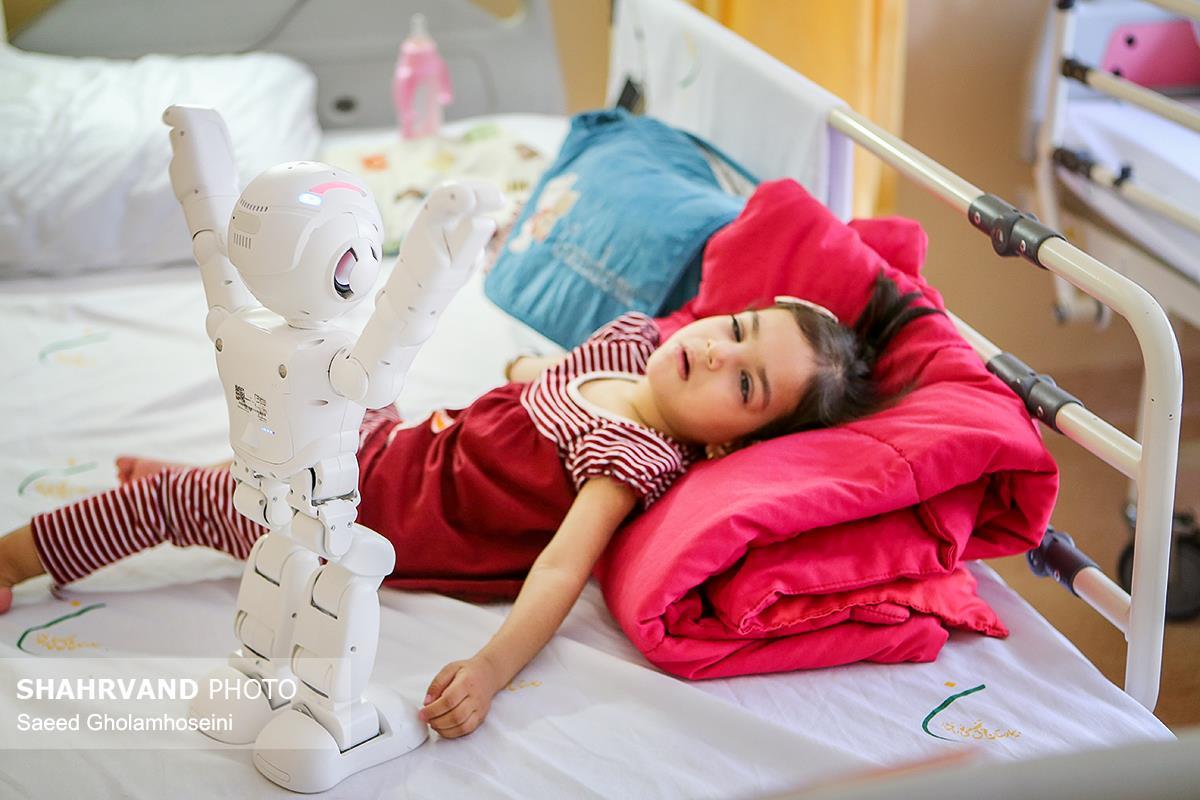 یمنا خاشعی دوسال و نیم که دچار فلج مغزی شده است،در بیمارستان نورافشار تحت درمان قرار دارد.با هدف بالا بردن توجه و تماس چشمی ربات با او بازی میکند.